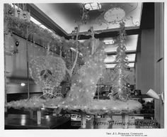 J.L. Hudson Company Department Store. The large display is affixed atop an interior retail display, and features a holiday Cinderella display, including a carriage, ornamented fir tree, illuminated snowflakes, and twinkle lights. Pocket books are visible in the display case in the background.