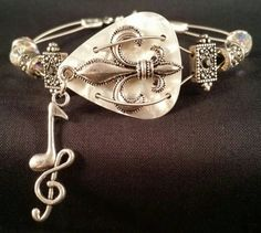 A 7.5 inch bracelet made from a guitar pick, guitar strings and swarovski crystals.