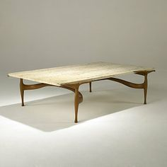 Dan Johnson; Travertine and Walnut 'Gazelle' Cocktail Table, c1955. from liveauctioneers.com