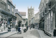 Two prams represent the only traffic in St Austell's attractive shopping street in this scene, which is dominated by the richly carved tower of Holy Trinity church. On the left, the windows of Lee's drapers shop display a sale of costumes, blouses and millinery, with many hats filling the right-hand window. Photo: St Austell, Fore Street 1912. #FrancisFrith #photography