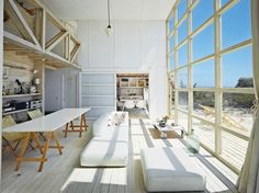 The northern facade, which faces the water, takes in the view via double-height windows in the main living room, plus terraces punched into the second floor.