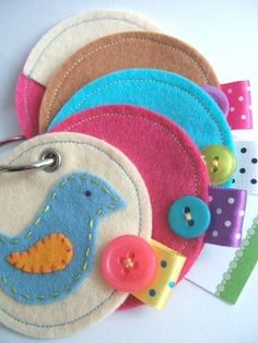 """Create a busy book for your toddler. Use children's books for ideas for each coloured circle. Put an activity on each side of the circle.   Use a colourful button and folded ribbon to help your child to """"turn"""" the circles.   Use a hole punch and hold together with a ring as in the photo."""