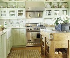 Why are stainless steel and ceramic tile such popular materials for a room that we want to be cozy and inviting? In this homey kitchen, soft celadon cabinets offer cottage appeal while the salvaged wood island exudes a warm patina. A display of vintage china and a nubby rug contribute to the kitchen's charm.
