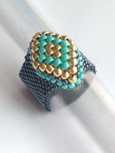 Anillo - Beadwoven - joyas Boho - semilla grano - abalorios - anillo con cuentas  Este es un anillo hermoso peyote. He utilizado rocallas japonesas en turquesa de hematita metálica oro. Anillo de banda flexible, trece filas de ancho.  Tamaño 8: 2 1/4 pulgadas o 5.7-5.8 centímetros (cm)  Hacer en todos los tamaños de anillos :) Si no sabes el tamaño de su dedo, utilizar una raya fina de papel que envuelve alrededor de tu dedo (Asegúrese de que el papel está por debajo de la articulación del…