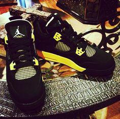 Black and yellow Jordan 4's