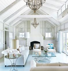 Pure inspiration: love the chandeliers, love the coral printed cushions, neutral sofas, glass-top tables, natural lamp, exposed beams and decommissioned fireplace that could also be mantled but this is minimalist Hamptons at its best!