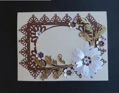 Floral topper silhouette studio on Craftsuprint designed by Lyn Simms - made by Maureen Garrigan - To make this file up I used my Silhouette Cameo...a cream A5 card blank..cream smooth card...bronze and white pearlised heavy paper and a gold textured card for the leaves. After cutting out the elements cutting extra flowers for the effect I wanted I attached the frame to the A5 cream card blank with Tombow glue then attached the cream oval to the frame with 1mm foam pads. I also used Tombow…
