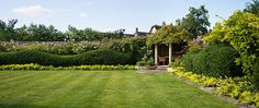 Credit: Andrew Lawson The Manor House, Armscote in Warwickshire. Designer Dan Pearson gives a conventional lawn with an Arts and Crafts corner pavilion a modern appeal by simple fringe plantings of Alchemilla mollis and a distinctive wavy-topped edge.