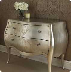 This is so pretty. The blog focuses on refurbishing a piece with metallic paints, but I just love the shape of this dresser and the floral pattern across the front.
