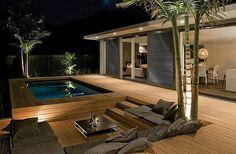 terrasse en bois ou composite, une terrasse moderne, piscine rectangulaire et palmiers: