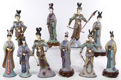 Lot 554: Asian Cloisonne Figurine Assortment; Including ten female court or soldier figurines holding flowers or swords with cloisonne bodies and carved heads; together with six carved wood stands
