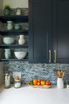 Diamond Cabinets painted in a deep ocean blue are set against a counter-to-ceiling backsplash of mosaic tile by The Tile Shop that suggests sea glass.