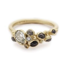 An alternative engagement ring featuring a beautiful tapering cluster of diamonds. Handmade in London, this is a unique, asymmetrical engagement ring.