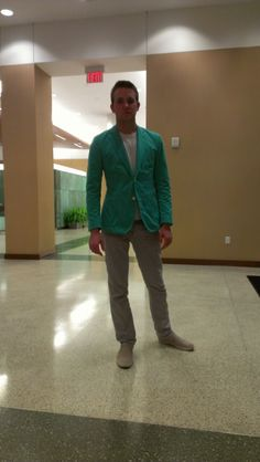 Green blazer with gray pants.