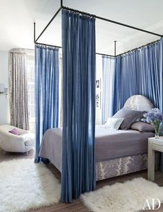 A child's bedroom by Stephen Sills features a custom-made bed curtained in a purple Castel fabric.