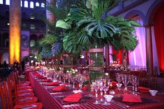Palm fronds, votives, and glass vases were prominent in event designer David Tutera's table design, adding to the tropical flavor of the evening. Description from bizbash.com. I searched for this on bing.com/images