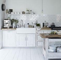 cuisine vintage blanche aménagée avec des armoires en bois blanchi et crédence en carreaux blancs