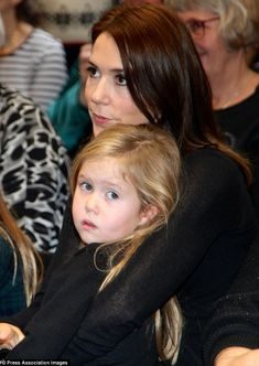 Cuddles all round: At one stage Princess Mary was seen snuggling into Princess Josephine who was considerably less smiley compared to her energetic twin brother