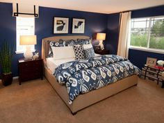 Dark blue and taupe make for a pleasing and restful color combination for this contemporary master bedroom. The room's focal point is the platform bed and headboard that duplicates the color of the carpeting for a blended effect.
