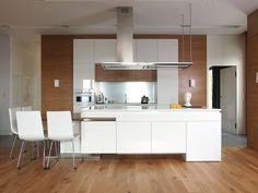 Bellissima cucina moderna con pavimento, rivestimento parete e mobili in legno e isola bianca