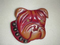 RARE BAKELITE BULLDOG BROOCH FROM THE LATE THIRTIES. IT IS APPROX. 2.5 INCHES X 2.25 INCHES. CHERRY RED WITH BUTTERSCOTCH COLOR HIGHLIGHTS. IVORY LOWER CANINE TEETH GLASS EYES AND BRASS STUD COLLAR.
