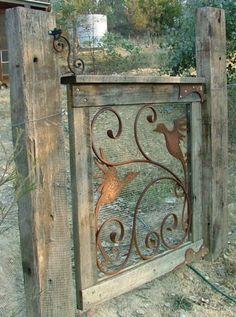 Tuinhek gemaakt van oud hout, metalen ornament en gaas.
