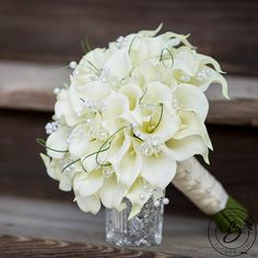 """""""Grassy Callas"""" large wedding bouquet with real touch calla lilies, crystals and bear grass This elegant design of the signature wedding flower, calla lily, is loaded with sparkling embellishments that catch the eye of even the most apathetic wedding guest. Bouquet that truly makes a statement! Let your special day be beautifully captured among the crystals and peaks of bear grass in this bridal bouquet to be treasured every day in your new life together. Made with over four dozen…"""