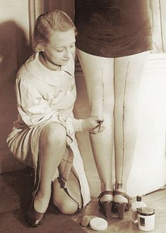 """1940's~This woman is painting a line on the back of the other woman's leg to look like she is wearing nylons. Popular """"back in the day""""!"""