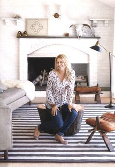striped rug, camel saddle stools, white exposed brick, dual fireplaces, grey sofa w a sheepskin
