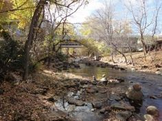 A view west along Boulder Creek. In the foreground several rock spires and in the back, a pedestrian bridge crossing the creek, all surrounded by trees .  This is taken before the 2013 floods which really changed the landscape of the creek.