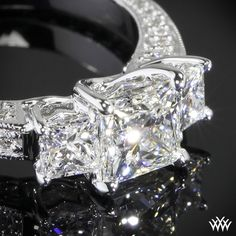 """Designed to thrill, the """"Coeur de Clara Ashley"""" 3 Stone Engagement Ring for Princess Cut Diamonds hits all the right notes. The beautiful lines join together to create three perfect hearts to hold your three perfect diamonds."""