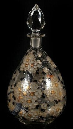 DELVAUX 1920'S ART GLASS PERFUME BOTTLE. (Circa 1920's) Delvaux French art glass perfume bottle, clear blown glass bottle with ground and polished pontil bottom, decorated with black, white and gilt blossoming branch overall decoration <3