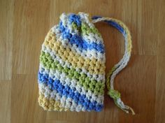 To attach the draw string easily: after crocheting the chain, tie off and leave a bit of yarn hanging from one end, then use a yarn needle to weave it through the first row of stitches below the bag opening. Tie off securely and snip off the extra yarn when finished.  Super Simple Soap Saver Crochet Pattern