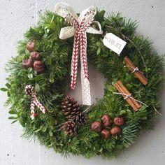 Julkrans i blandat ris gran, lingon och tall, dekorerad med kanelstänger, kottar, kastanjer, vackra band och en liten vit träskylt med texten god jul ♥