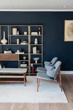Two blue mid-century modern chairs sit side by side facing a marble top coffee table positioned on a white wool rug in front of a styled 3 piece brass and wood shelving unit positioned flush against a deep blue wall illuminated by recessed lighting.