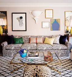 An ottoman covered in a Scalamandré velvet is juxtaposed by a diamond-patterned wool rug. Brightly colored damask throw pillows complement an abstract painting.