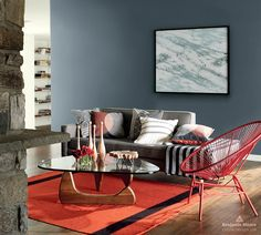 An intimate living room with gray accent wall, stone mantle, wood floors and red area rug is equal parts contemporary and cozy.