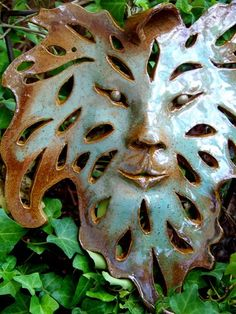 This leaf face is modeled out of a slab of brown stoneware clay. Glazed with robins egg blue , amber and copperhead. It measures 10 L x 9 W. Great accent for your garden or home.