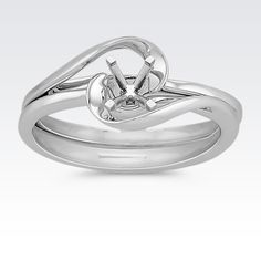 Just as two special people come together in marriage, this delightful wedding set fits together like pieces to a puzzle. This wedding set, crafted in quality 14 karat white gold, features a swirl design that forms at the top and one side of the set contains a flat edge making it easy to add any additional band to celebrate an anniversary. Complete this setting with the gemstone of your choice.