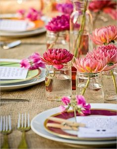 Simple wedding table centres... dahlias in jam jars. For more inspiration visit www.weddingsite.co.uk