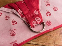Ladybirds Eros Ring Sling w/ Highlands shoulder.  Cute retro Ladybirds in classic red and ecru. 100% organic combed cotton, suitable for all. Approx 260gsm £82.00 Released 09/20/2015