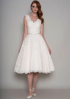 Alluring tea length lace wedding dress with ivory corded lace overlay, trimmed with a narrow satin bow belt. V-neck sleeveless bodice topped by a-line skirt.