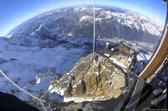 A stunning view from a glass cube with a see-through bottom suspended from the Aiguille du Midi mountain of the landscape, including Mont Blanc, Europe's highest mountain.