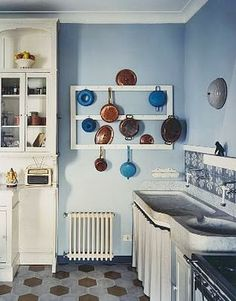 Blue kitchen in an Italian villa with hexagon tile floor and a wall mounted pot rack