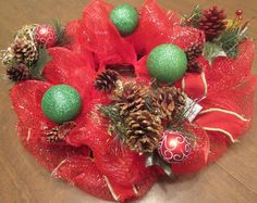 This holiday centerpiece is approximately 16 inches across and was made using a bright red deco mesh and decorated with pine cones,