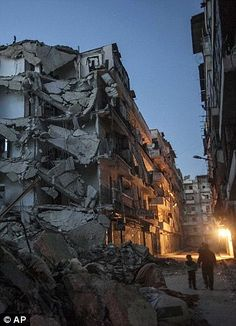 Residents walk past damaged buildings due to heavy fighting between Free Syrian Army fighters and government forces in Aleppo, Syria, in a picture taken in October 2012
