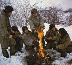 Czechoslovak People's Army tankmen taking a break around a fire during winter maneuvers.