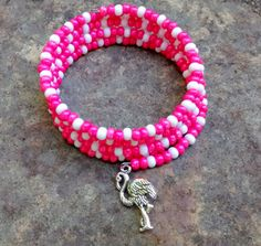 Four coil round pink and white memory bracelet with a flamingo charm. Beads: Opaque luster pink and white seed beads. No clasp is needed as the bracelet easily wraps around your wrist.