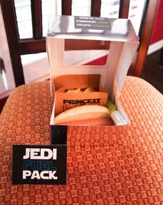 jedi fuel pack: We had a lunch break, where we served Jedi Fuel Packs, which were silver cupcake boxes filled with a Darth Dog (hot dog), Princess Lays (potato chips), and Light Sabers (green grapes on a long toothpick on the end of a foil covered wine cork). Jedi Juice was served in individual R2D2 and Darth Vader sippy cups and for the adults, we provided Yoda Soda (Sprite) and Wookie Water.