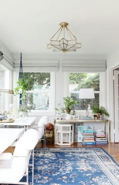 Love this rug and the way the room feel light and airy with the green plants. Not a big fan of the gold fixtures.